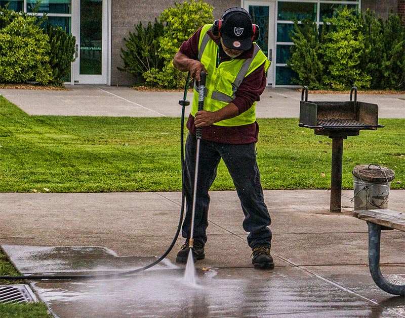 A member of Seattle Parks and Recreation's maintenance team washing a picnic area.