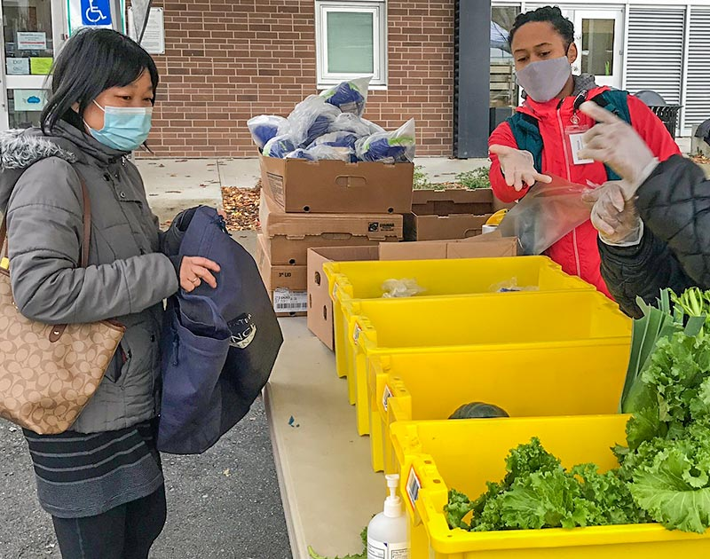 Staff and a resident participating in a food pickup program.